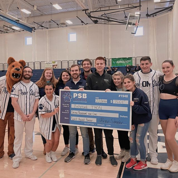 Dance and cheer teams holding a giant check for $7,000 to be donated to THON