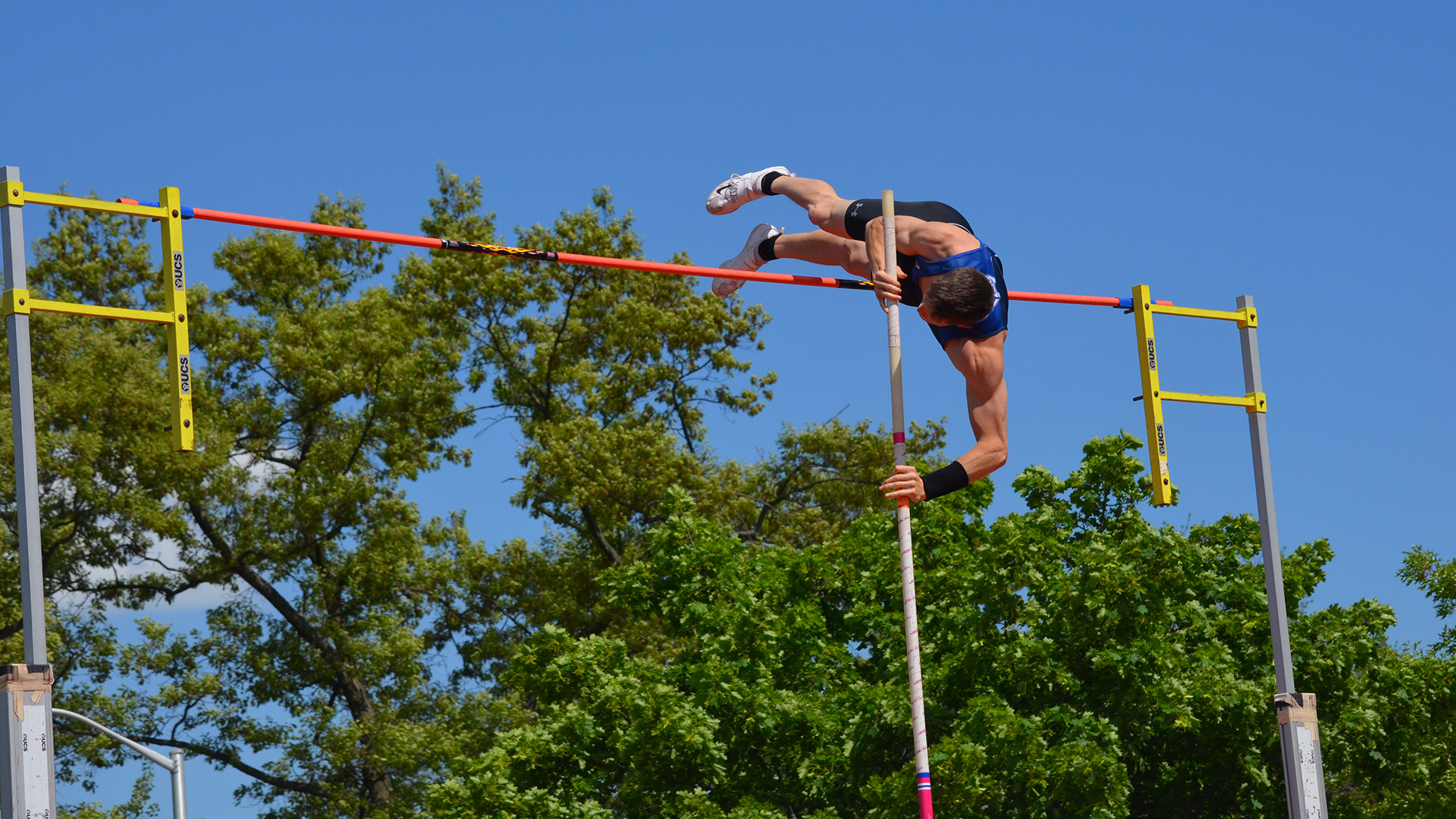 Track and field athlete attempts a pole vault.