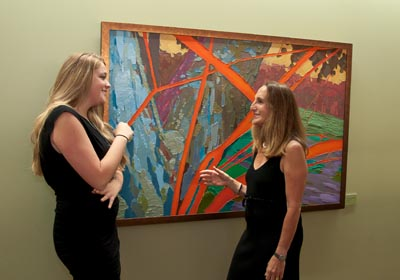 Two women standing in front of a colorful painting