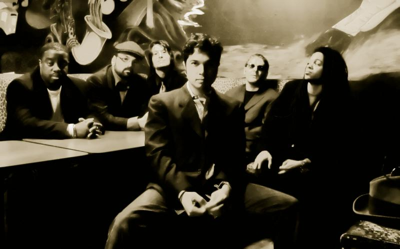 Black and white photo featuring group of musicians sitting looking at the camera