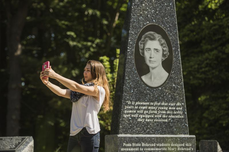 Student taking picture in front of the Mary Behrend Monument.