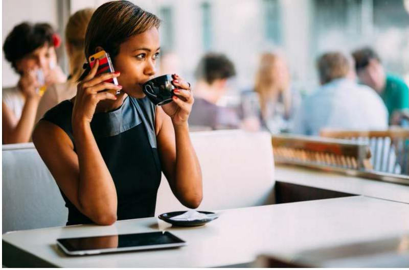 Women drinking coffee with a phone at her ear. Sitting in a cafe