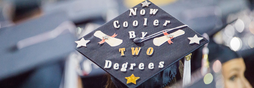 A Penn State Behrend graduate shows off a decorated mortarboard at commencement.