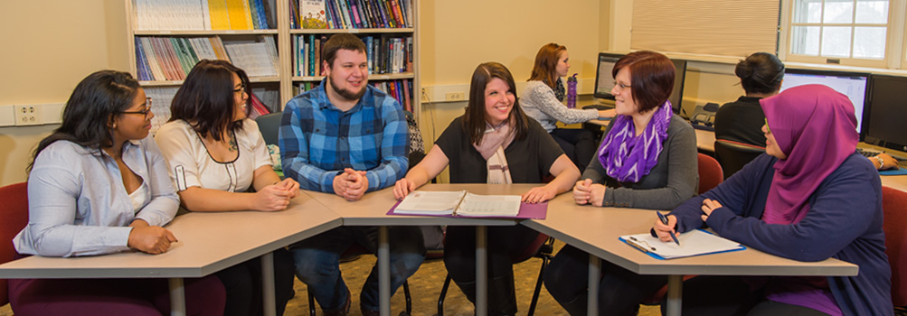 Applied Clinical Psychology students participate in a workshop at a seminar table.