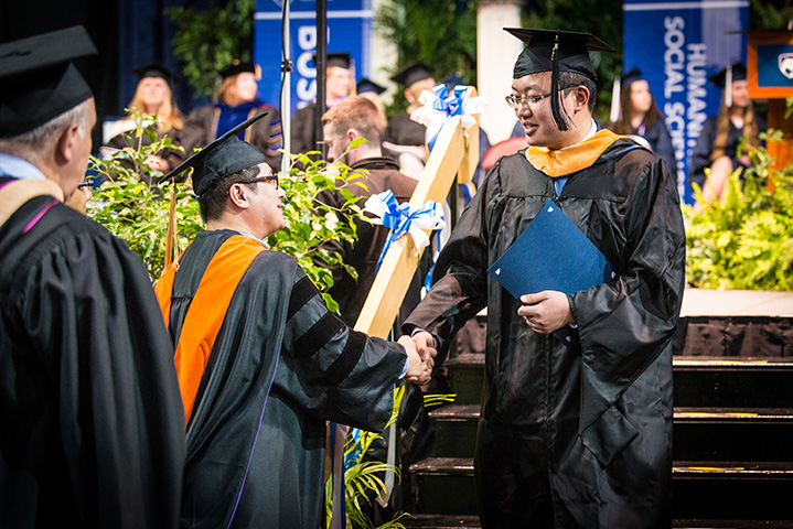 Penn State Behrend graduats shake hands at commencement