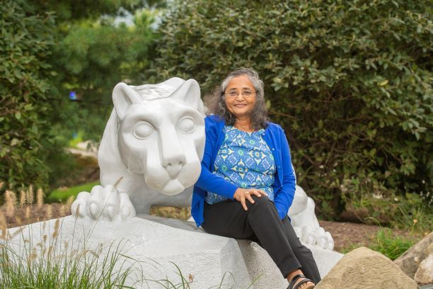 Alumna Nishi Gupta sits at the Nittany Lion shrine at Penn State Behrend