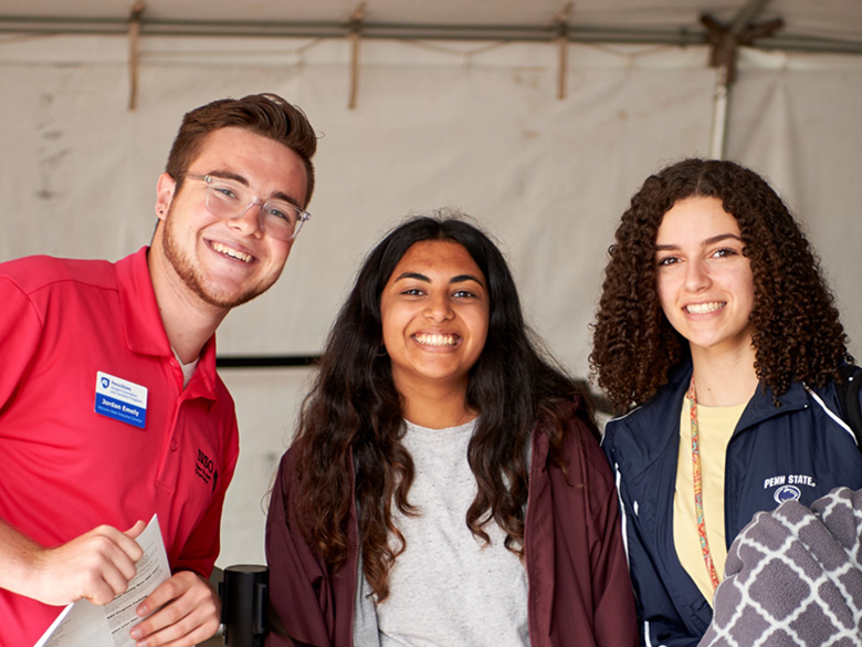 Three students pose together in a group at a new student orientation event.