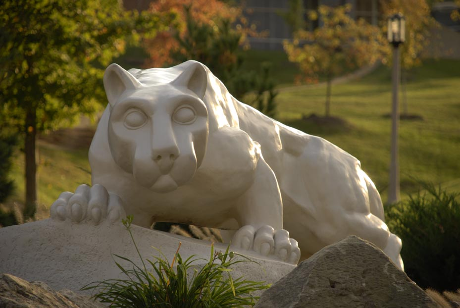 A statue of the Behrend Lion in front of autumn trees