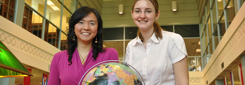 Two female students at Penn State Behrend stand behind a globe.