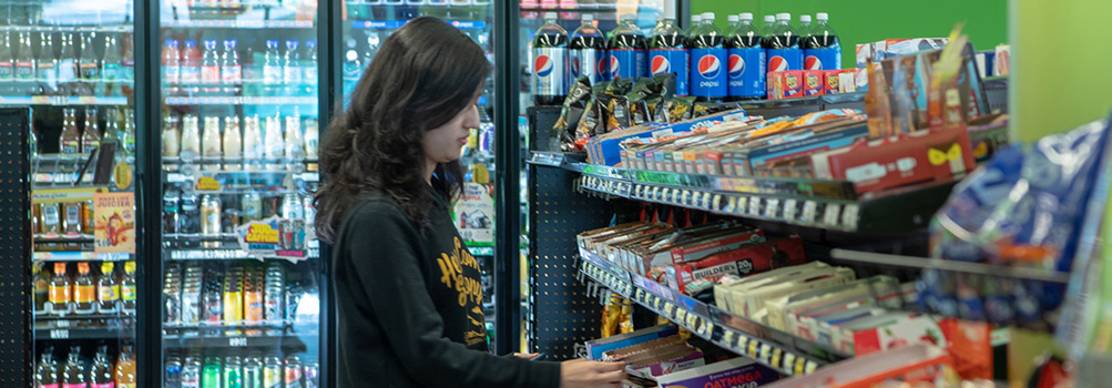 A student at Penn State Behrend chooses from various brands in the on-campus convenience store, The Galley.