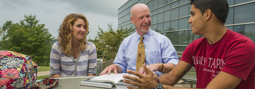 A project and supply chain professor at Penn State Behrend meets with two students