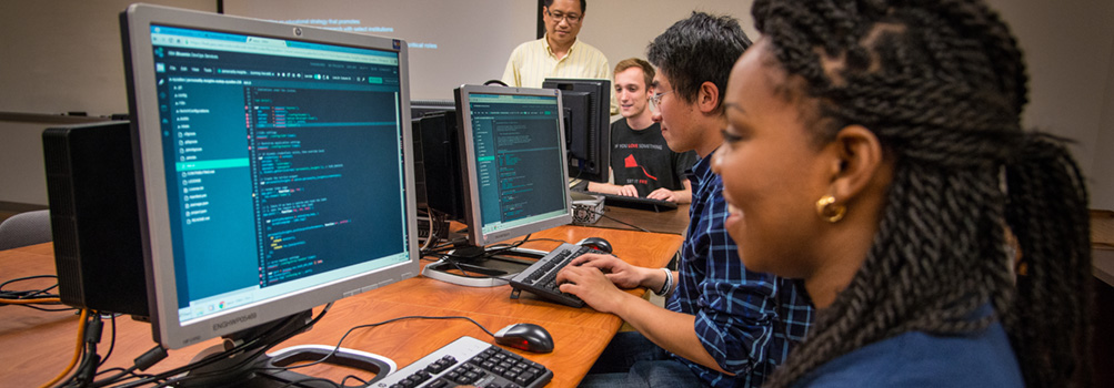 A professor at Penn State Behrend advises three students working on computer code.