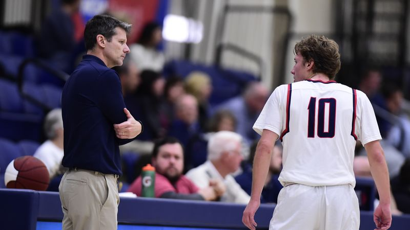 Penn State Behrend men's basketball coach Dave Niland talks with his son, Andy Niland, during a game.
