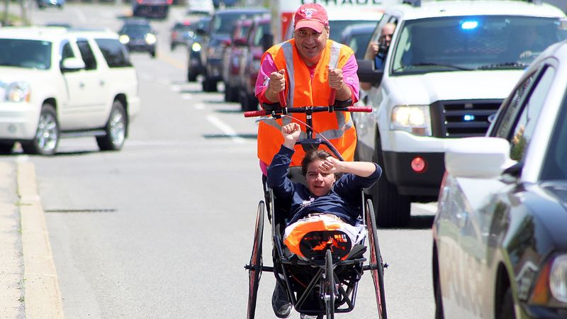 Dan Perritano pushes his daughter in a wheelchair on the side of a road.