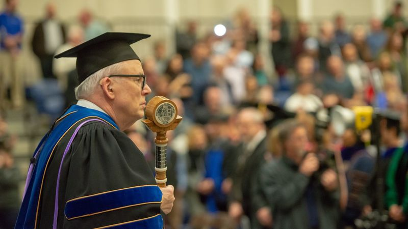 Penn State Behrend faculty member John Gamble carries the college mace at a commencement ceremony.