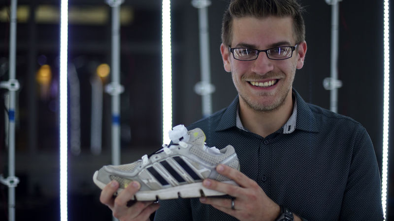 Penn State Behrend graduate Wes Hall holds the Lace-N-Lock shoe-tying device.