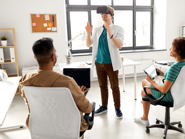 A young man wearing VR glasses demonstrates to two seated business people.