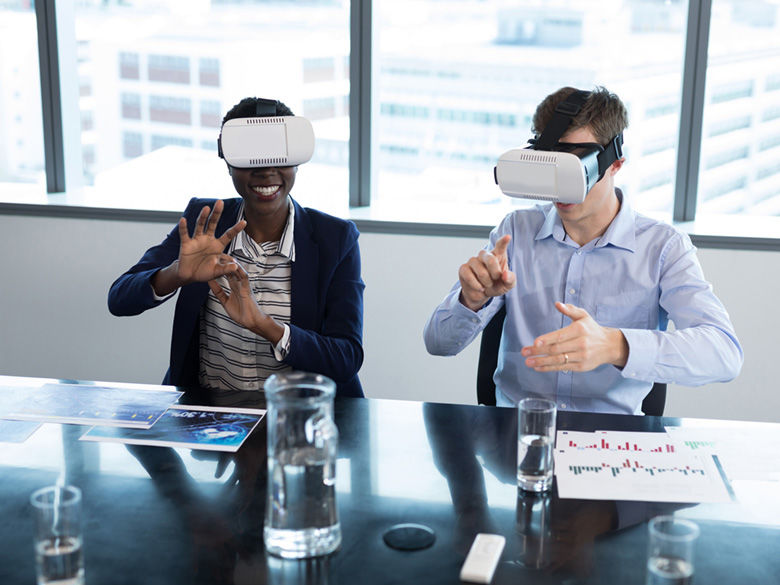 Smiling woman and man using virtual reality headsets in office.