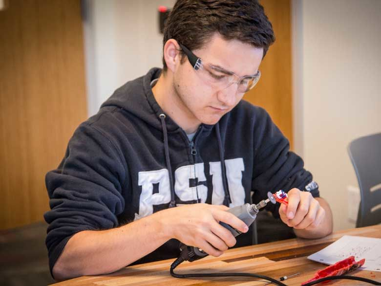 A Penn State Behrend student uses a hand tool.