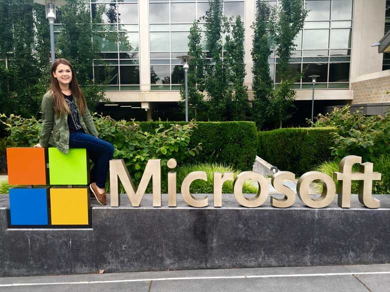 A Penn State Behrend student visits the Microsoft offices, stopping to pose for a photograph on a sign of the Microsoft logo.