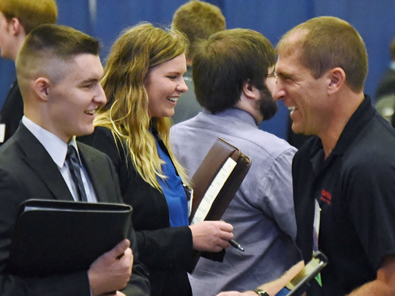 A recruiter meets with a student wearing a suit at Penn State Behrend's Career and Internship Fair.