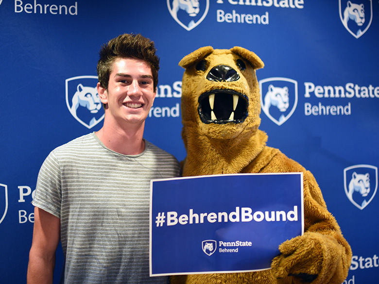 Male student with lion mascot holding #BehrendBound sign.