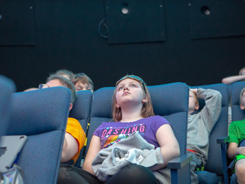 Middle school students attend a planetarium show.