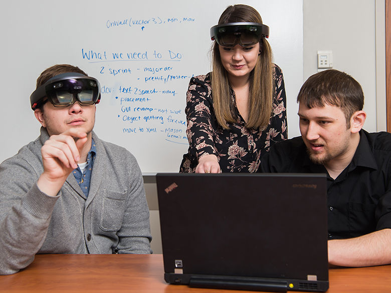Students use virtual reality headsets and a laptop.