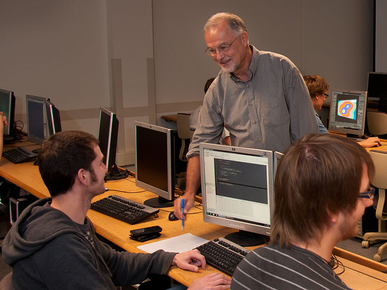 An instructor works with students in a computer lab.