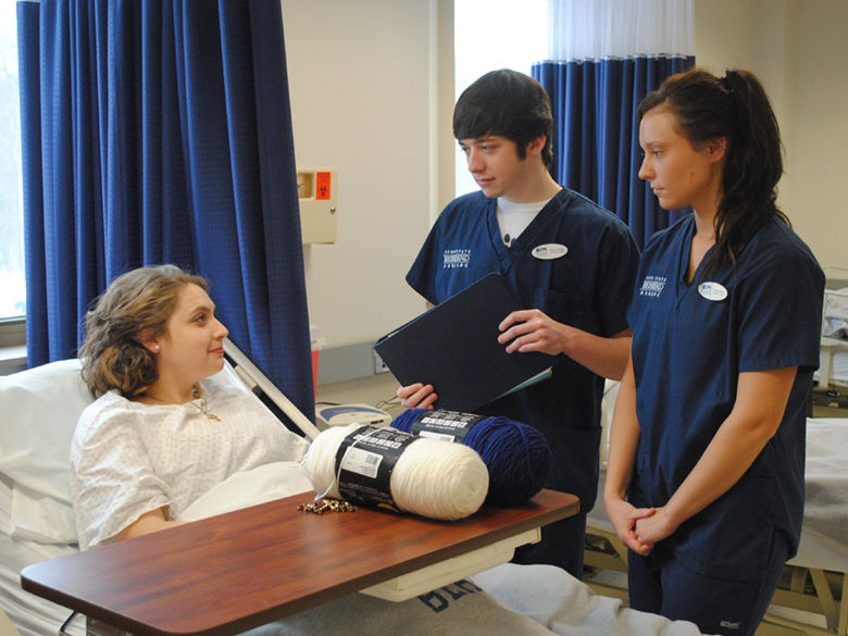 Two nursing students speak with a student acting as a patient.