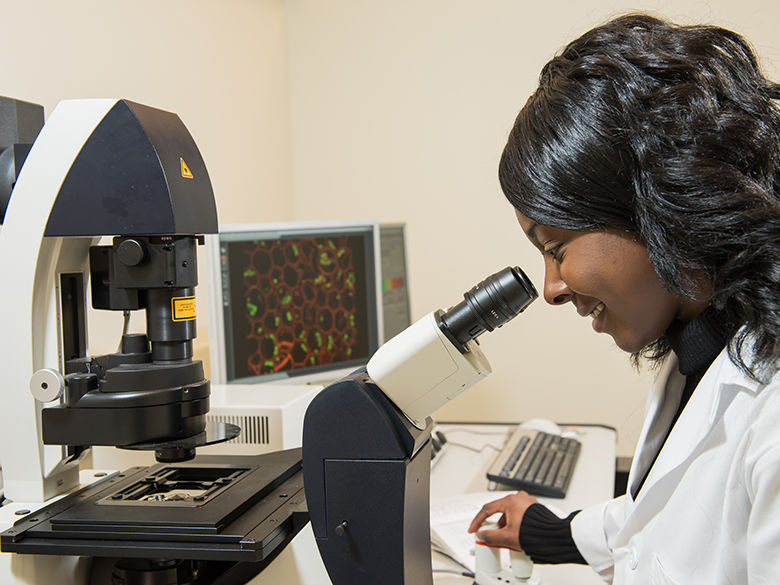 A female student looks through a microscope.