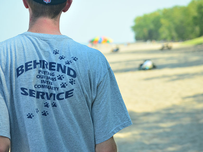 Student wearing Behrend Service t-shirt participates in service project at Presque Isle State Park beach.