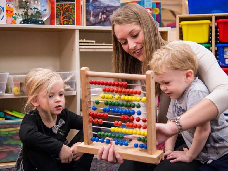 A Penn State Behrend student helps toddlers learn to count using an abacus.