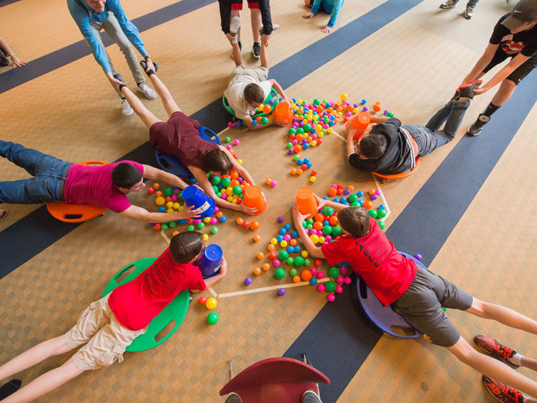 Students play a game with colorful balls at a CORE event.