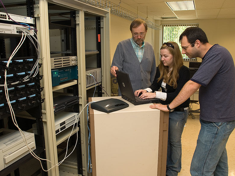 Penn State Behrend I.T. students work with a faculty member to program a rack-mounted server.