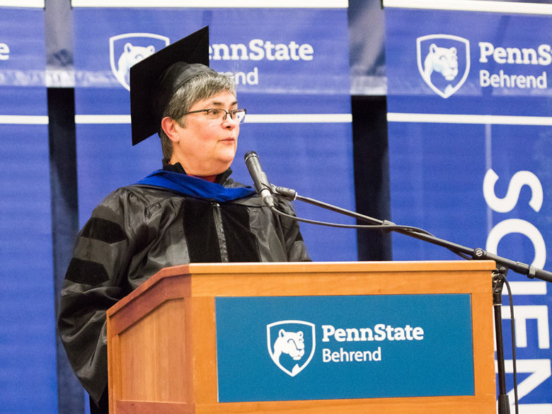 A faculty member wearing academic regalia gives the commencement address.