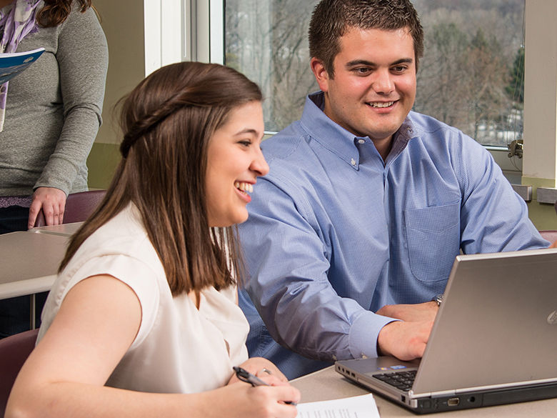 Two Behrend Master of Professional Accounting students studying at a laptop computer