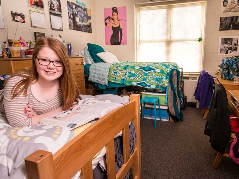 A Penn State Behrend female student studies in her tastefully decorated dorm room.