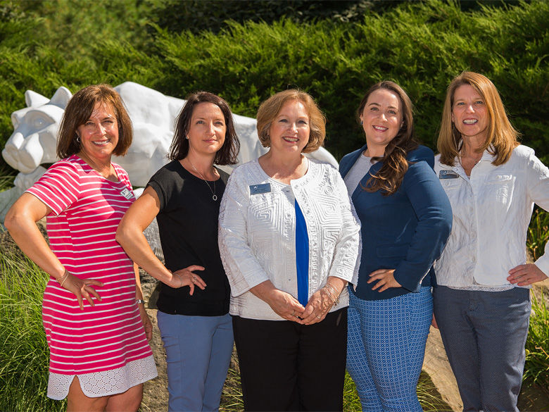 Five female Penn State Behrend staff members stand by the Behrend Lion Shrine.