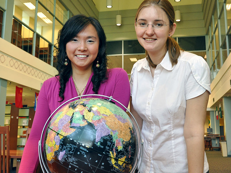 Two students stand behind a globe.