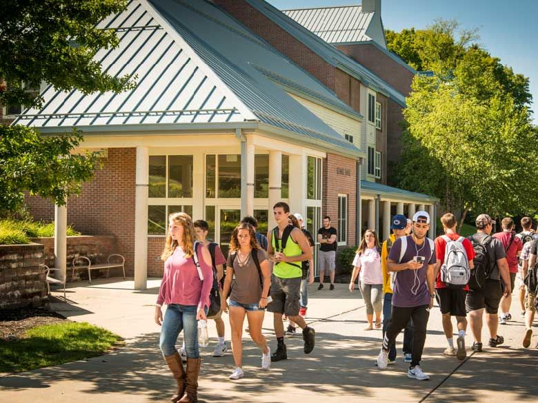 Students walk by Senat Hall on a warm day.