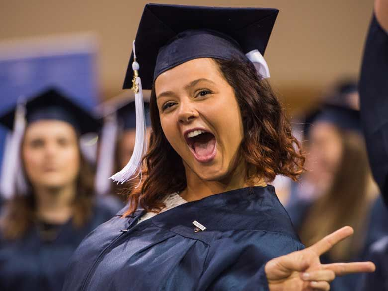 A female graduate in cap and gown makes a victory-sign gesture at commencement.