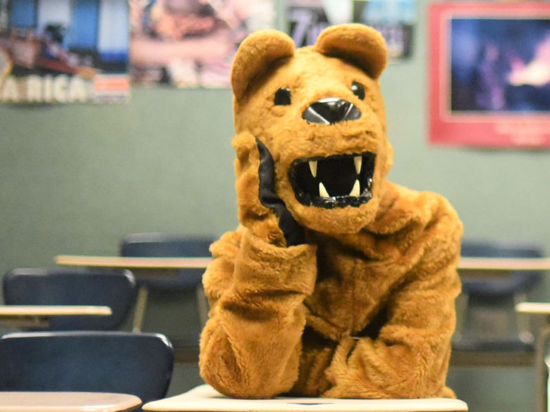 Lion mascot sits in a classroom