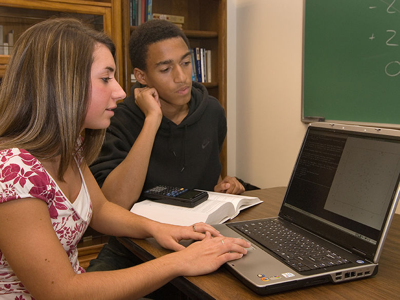 Two students work together using a laptop computer, a notebook, and a calculator.