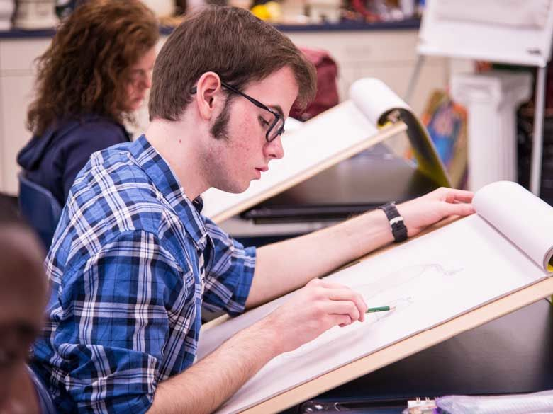A student draws in a sketchbook.