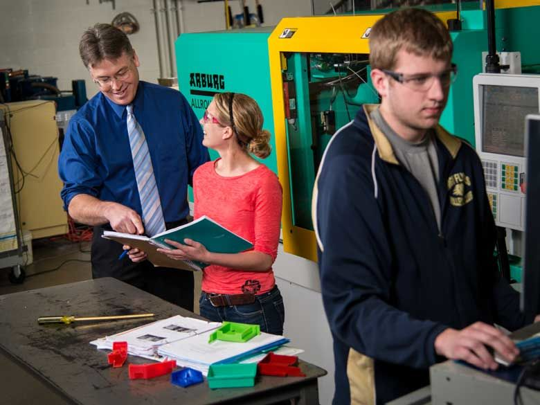 Two students learn from a professor in an engineering lab at Penn State Behrend in Erie, PA.