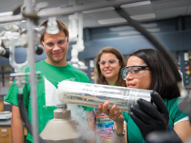 Matthew Silbaugh, Jackie Gowen, Grace Galinato work in a chemistry lab.