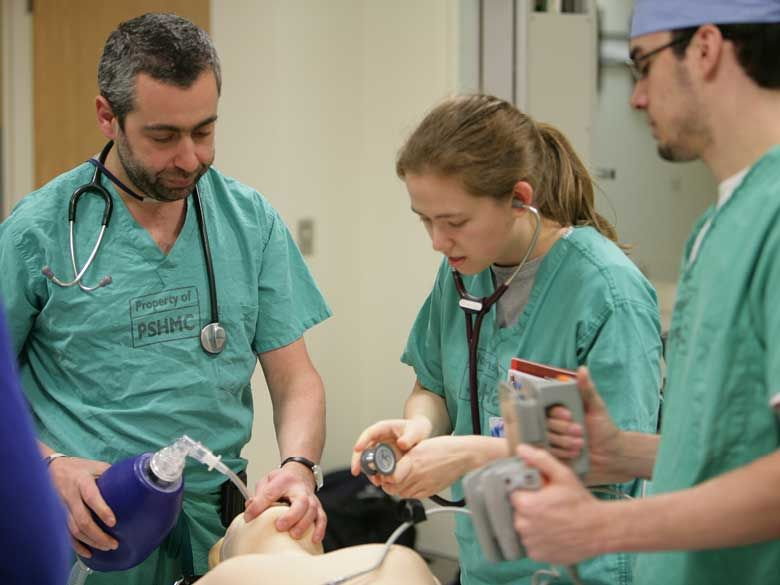 Two students learn pre-medical skills from a faculty member at Penn State Behrend.