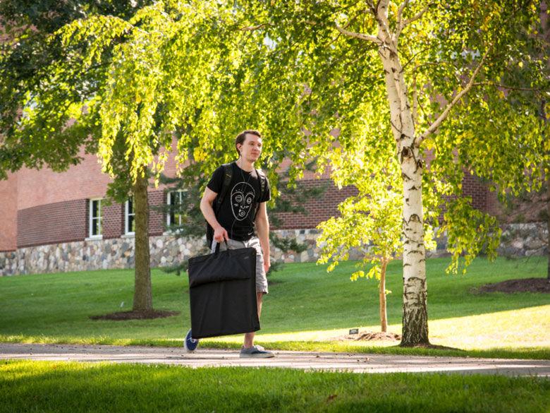 Penn State Behrend student walks across campus carrying an art portfolio.