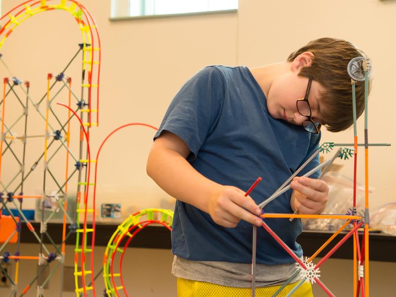 A boy uses a toy building set.
